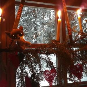Ikkunan edessä roikkuu joulukoriste, jossa kynttilöitä.