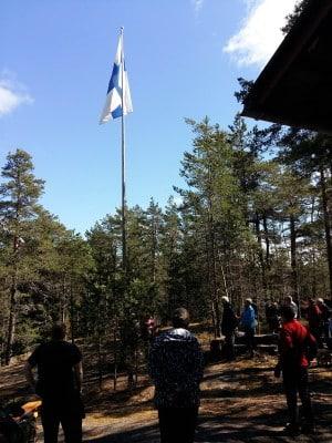 Suomenlippu salossa mökin pihassa, ympärillä ihmisiä.