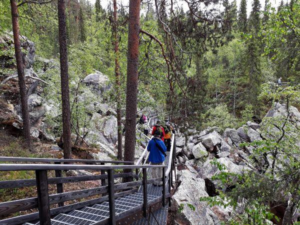 Ihmiset kävelevät jonossa rakennettuja metalliportaita pitkin kivikon yli.